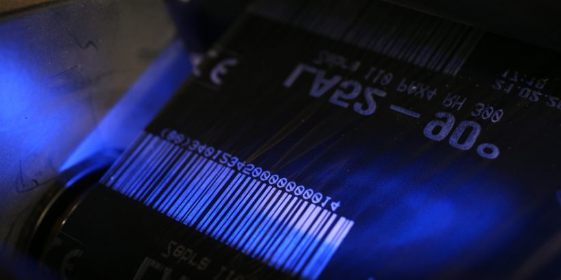 A white barcode printed over a dark surface